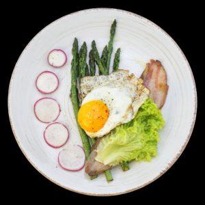Завтрак из жареной спаржи, яичницы и бекона